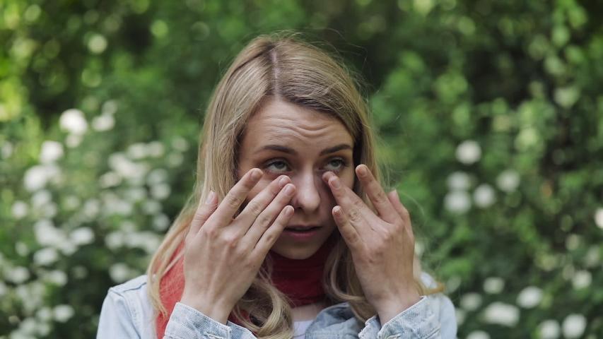 Young beautiful woman rubs her eyes standing against the background of flowering trees. Allergy, rhinitis, eye diseases, sinus pressure pain. | Shutterstock HD Video #1033095617