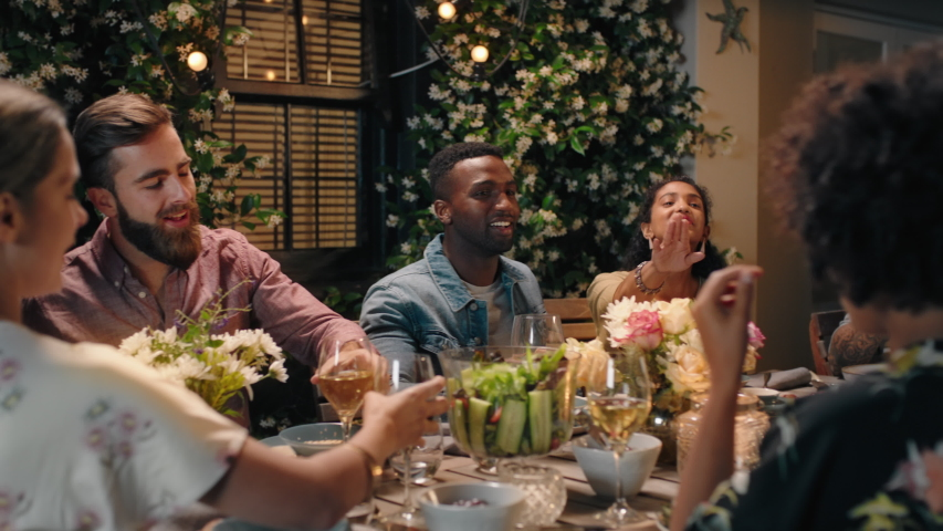 Group of friends celebrating evening dinner party sharing homemade meal enjoying casual conversation having fun weekend reunion relaxing on calm summer night outdoors 4k footage   Shutterstock HD Video #1033104686