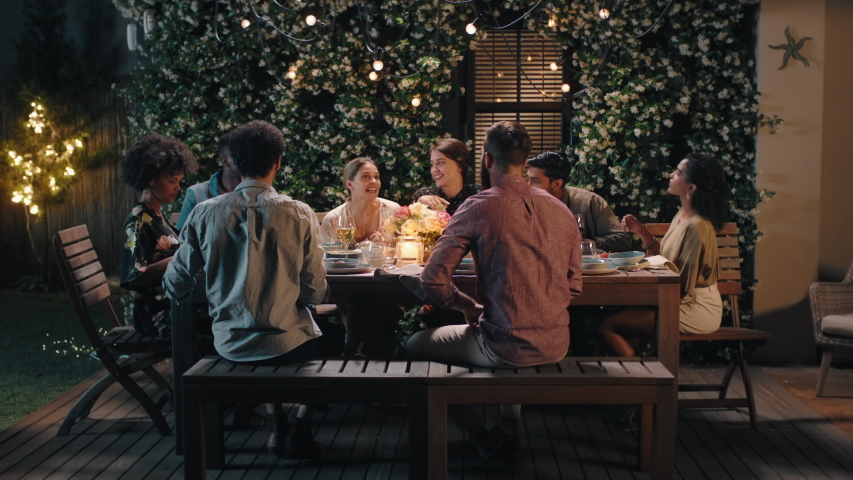 dinner party friends celebrating evening together sharing homemade meal enjoying casual conversation having fun weekend reunion relaxing on calm summer night outdoors 4k footage #1033105532