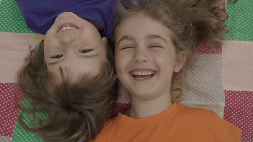 Friends selfie. Excited young children playing lying on the bed and taking a selfie. Little brother and sister monkeying on camera and kissing. Family taking a selfie with a smartphone. Close up.   Shutterstock HD Video #1033107908