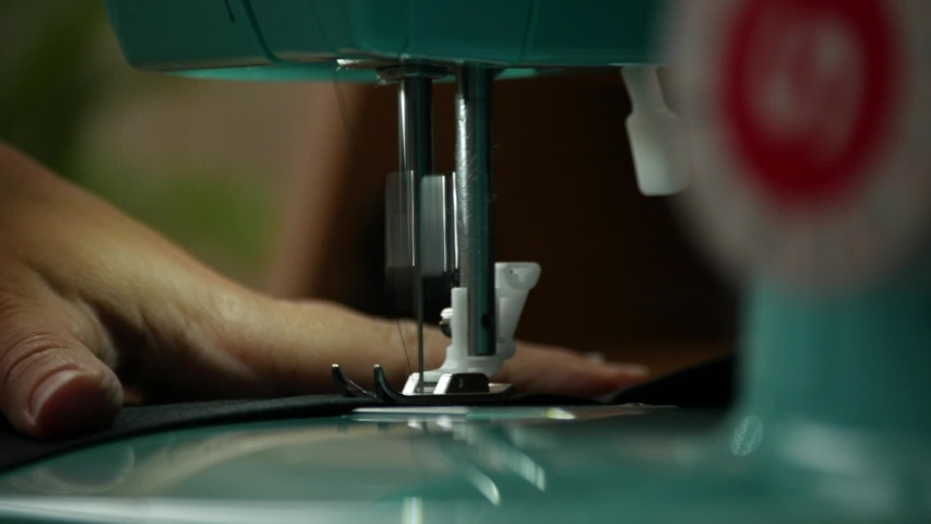 A female hand pushes material through a sewing machine | Shutterstock HD Video #1033109090