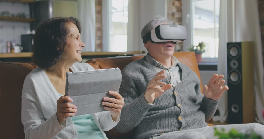 Portrait of elderly couple using tablet computer and virtual reality glasses sitting in living room. Senior and retired people using modern technologies