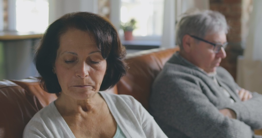Beautiful pensive old couple having conflict and sitting offended apart on couch at home