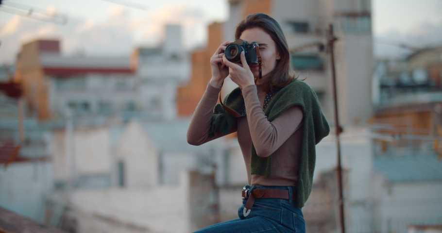 Attractive young girl in hipster outfit using retro camera on the rooftop in the old part of the city of Barcelona looking with friendly smile admiring the city, People Lifestyle Hobby, Slow Motion | Shutterstock HD Video #1033111007