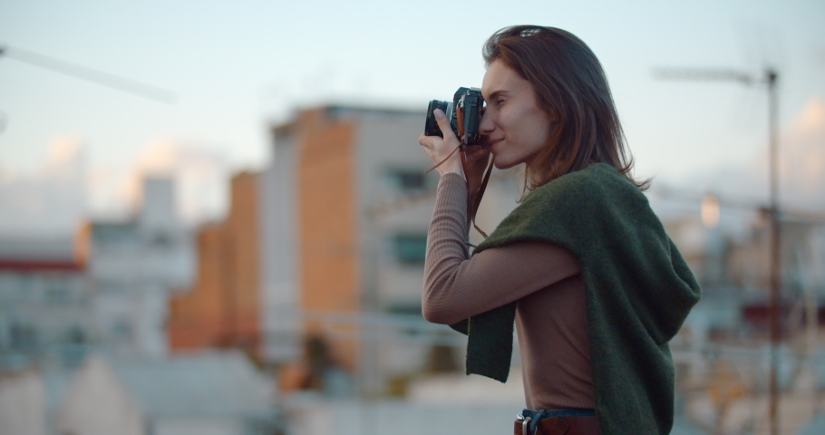 Attractive student girl in casual outfit spends time outdoors capturing photo on a film camera enjoying a beautiful evening in the old city of Barcelona, Lifestyle People, Slow Motion | Shutterstock HD Video #1033111016