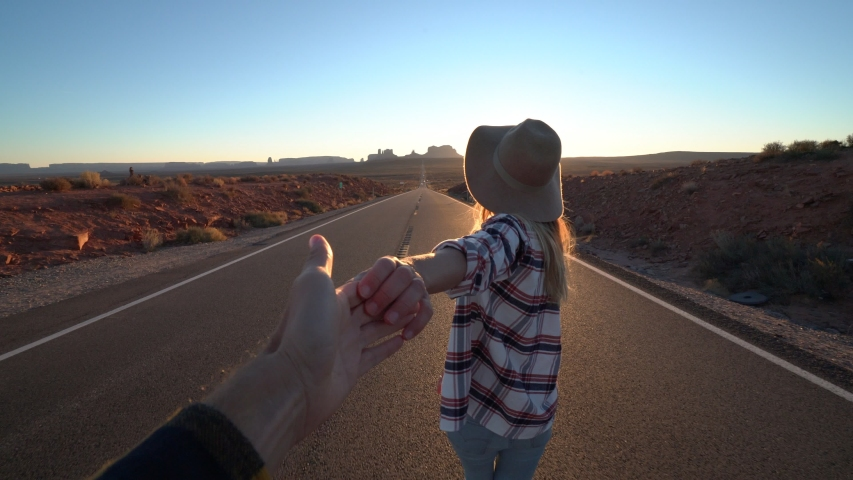 Follow me to concept; young woman leading boyfriend on empty highway in USA at sunset; Couple holding hands following each other near Monument Valley .leading the way | Shutterstock HD Video #1033112762