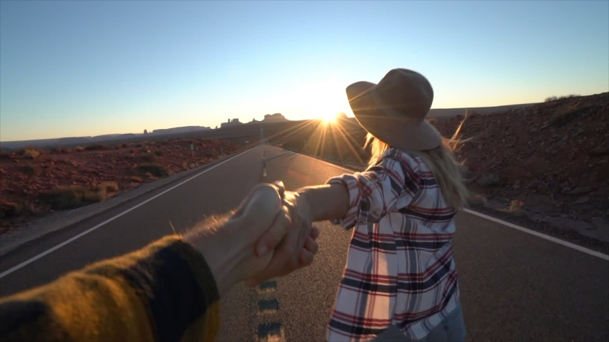 Follow me to concept; young woman leading boyfriend on empty highway in USA at sunset; Couple holding hands following each other near Monument Valley - slow motion  | Shutterstock HD Video #1033112765