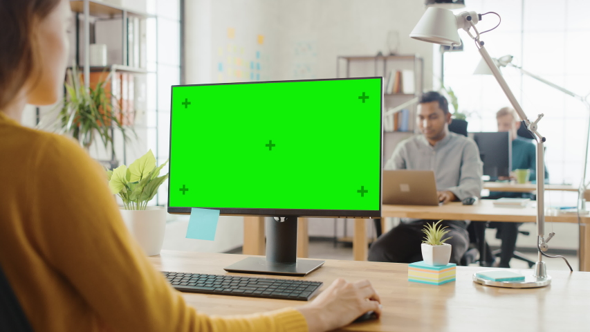 Over the Shoulder: Creative Young Woman Sitting at Her Desk Using Desktop Computer with Mock-up Green Screen. Bright Office where Diverse Team of Young Professionals Work on Computers | Shutterstock HD Video #1033113320