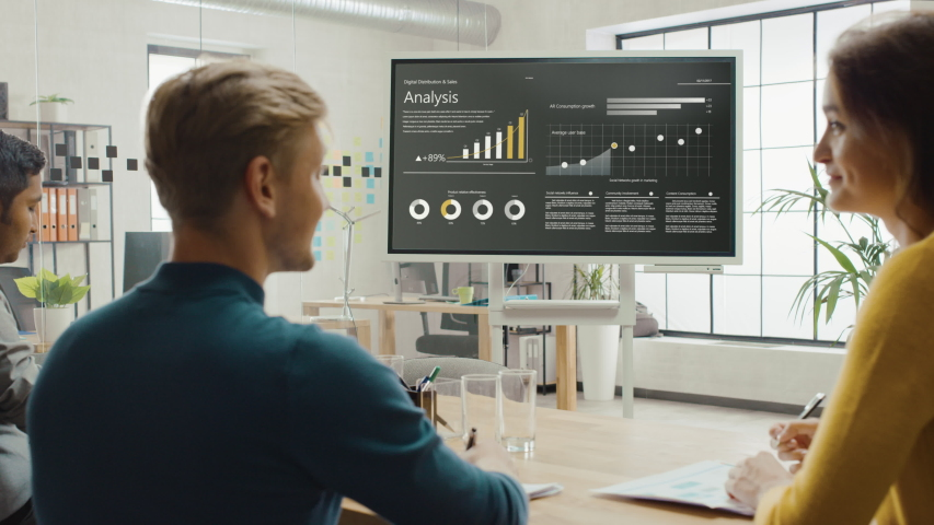 Team of Analytics, Economists and Young Businesspeople Hold Meeting Presentation use Shows Digital Interactive Whiteboard with Growth Analysis, Charts, Statistics and Data. People Work in Office Royalty-Free Stock Footage #1033113356
