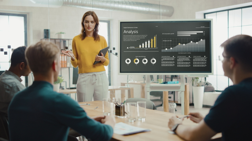 Female Chief Analyst Holds Meeting Presentation for a Team of Economists. She Shows Digital Interactive Whiteboard with Growth Analysis, Charts, Statistics and Data. People Work in Creative Office Royalty-Free Stock Footage #1033113362