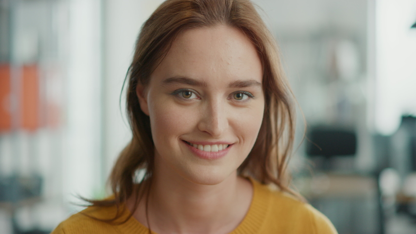 Portrait of Beautiful Young Woman with Red Hair Wearing Yellow Sweater Looking Up to the Camera and Smiling Charmingly. Successful Woman Working in Bright Diverse Office
