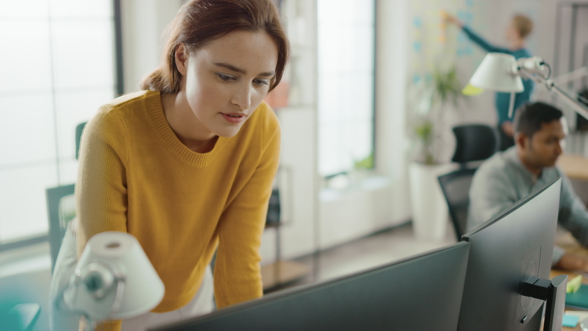 Beautiful and Creative Young Woman Sitting at Her Desk Using Laptop Computer. In the Background Bright Office where Diverse Team of Young Professionals Work Royalty-Free Stock Footage #1033113479