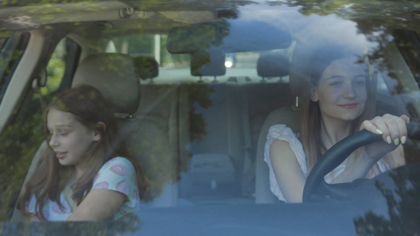Front view two attractive girls driving a car through city on sunny day. Two siblings friendly sisters having fun doing dancing moves into music while sitting inside the car.