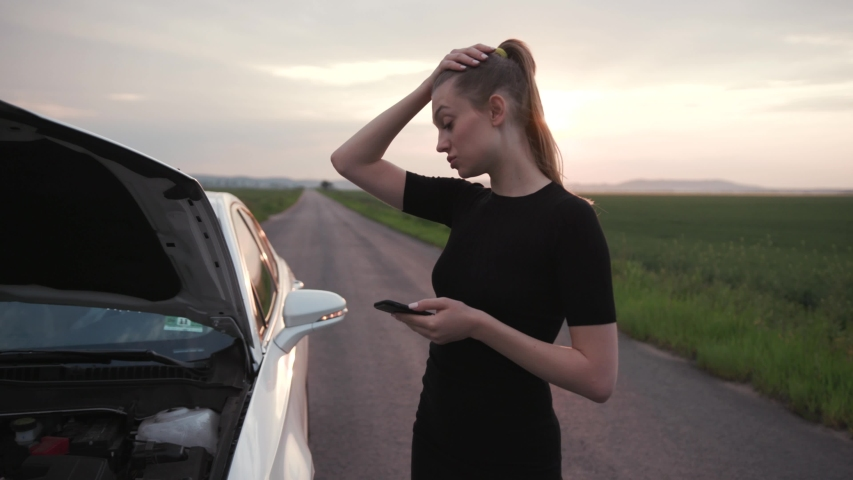 Nervous young woman stand use phone at sunshine looking at engine of breakdown car at the field alone automobile girl help lost road trouble upset side transportation travel close up slow motion
