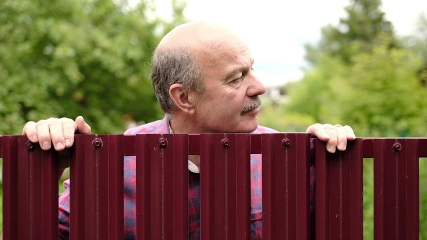 Mature caucasian man carefully watching over the fence. Concept of curious neighbors and private life | Shutterstock HD Video #1033155320