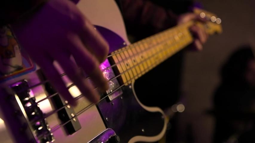 Strumming bass guitar strings in slow motion