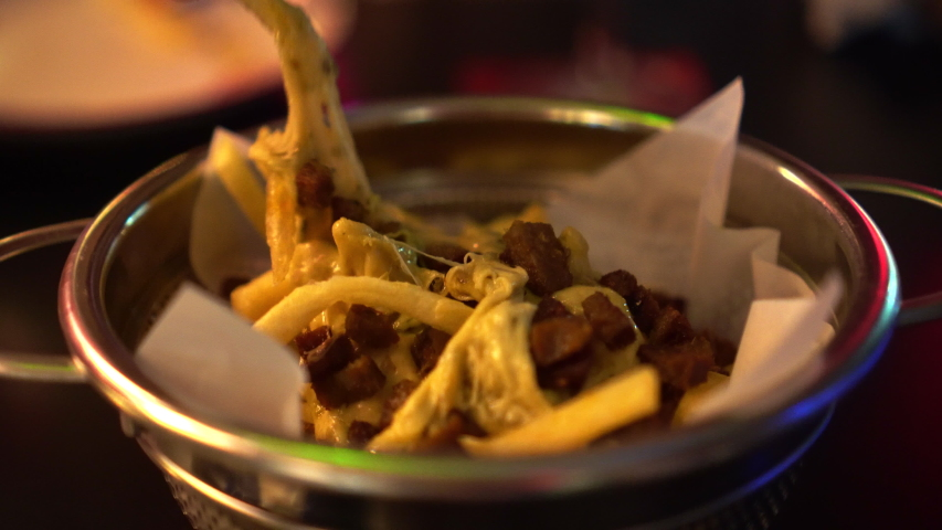Eating cheesy fries in red neon night club   Shutterstock HD Video #1033170287