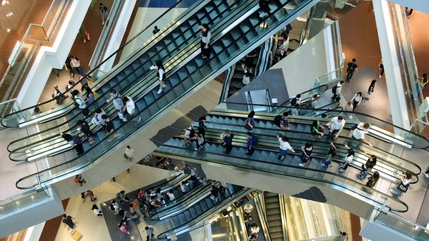 Time lapse of crowded people in shopping mall. Escalators in modern shopping mall.