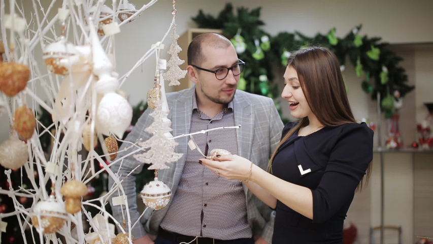 The loving couple selects the Christmas decorations in the supermarket. A woman considering Christmas balls and offers them to buy his husband. #1033184006