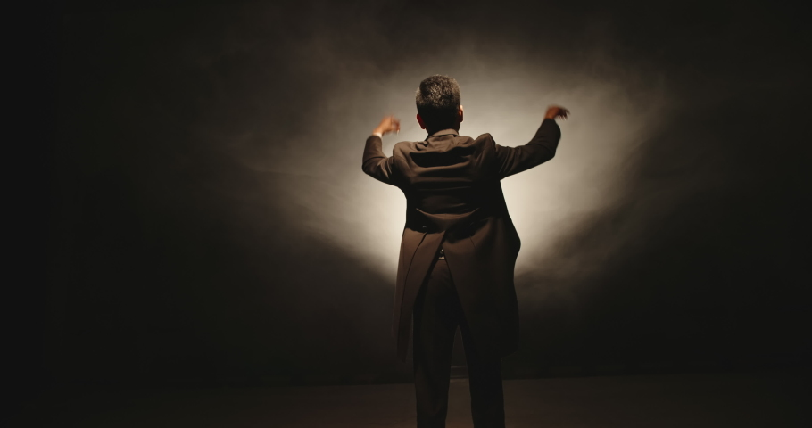 Unrecognizable Male orchestra conductor controlling music in orchestra pit by movement of his hands and white baton, studio shot on black background 4k footage