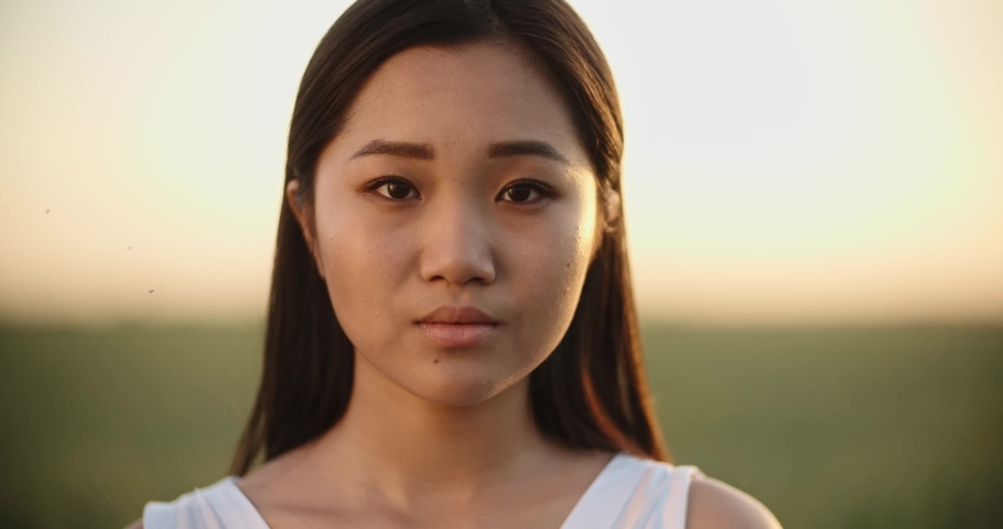 Cute asian girl standing in the wheat field during sunset as the wind blows her hair, looking at camera - close up portrait shot 4k footage #1033184255