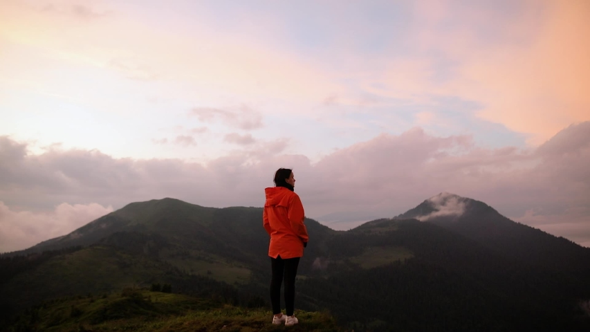 Camera follows hipster millennial young woman in orange jacket running up on top of mountain summit at sunset, happy and drunk on life, youth and happiness | Shutterstock HD Video #1033184627