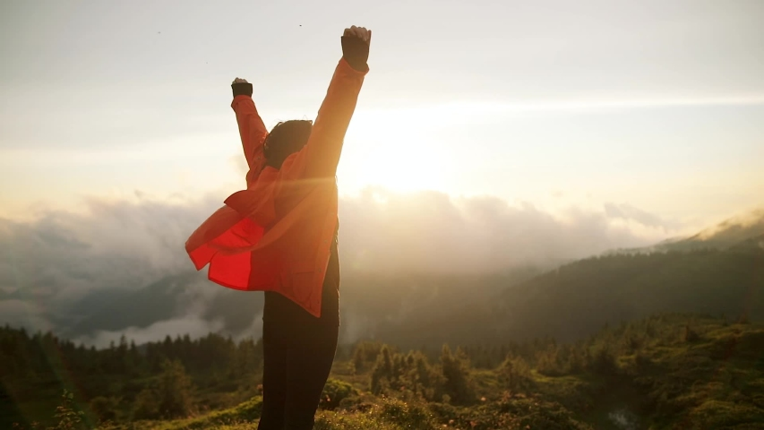 Camera follows hipster millennial young woman in orange jacket running up on top of mountain summit at sunset, jumps on top of rocks, raises arms into air, happy and drunk on life, youth and happiness
