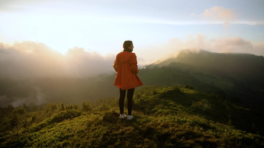 Hipster millennial young woman in orange jacke on top of mountain looking at sunset view | Shutterstock HD Video #1033184663