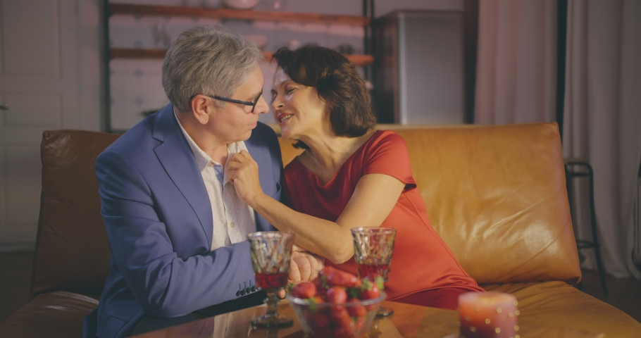 Affectionate attractive elderly couple sitting together on a couch, having romantic dinner and kissing | Shutterstock HD Video #1033189145