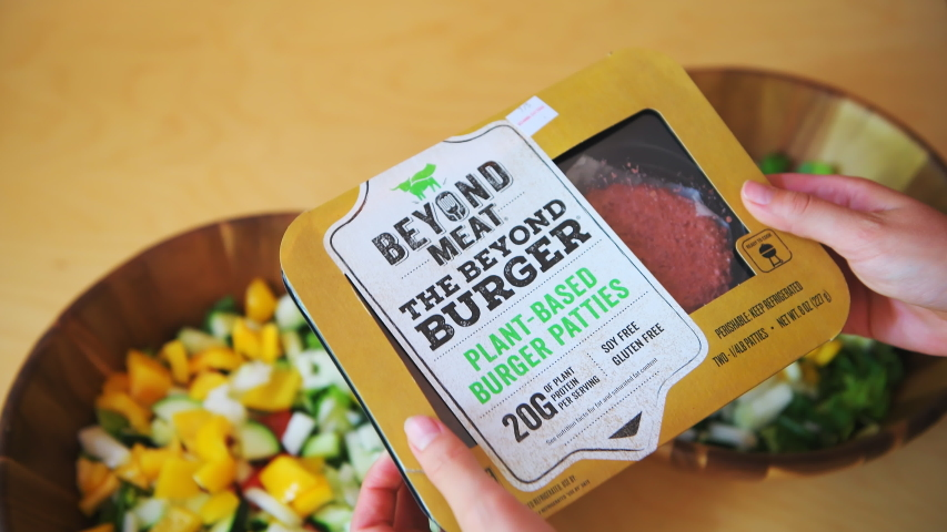 Aspen, USA - June 29, 2019: Beyond meat plant-based protein burger package with woman holding brand by salad bowls