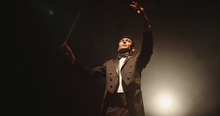 Asian symphony orchestra conductor wearing suit is directing musicians with movement of baton, isolated on black smokey background 4k footage