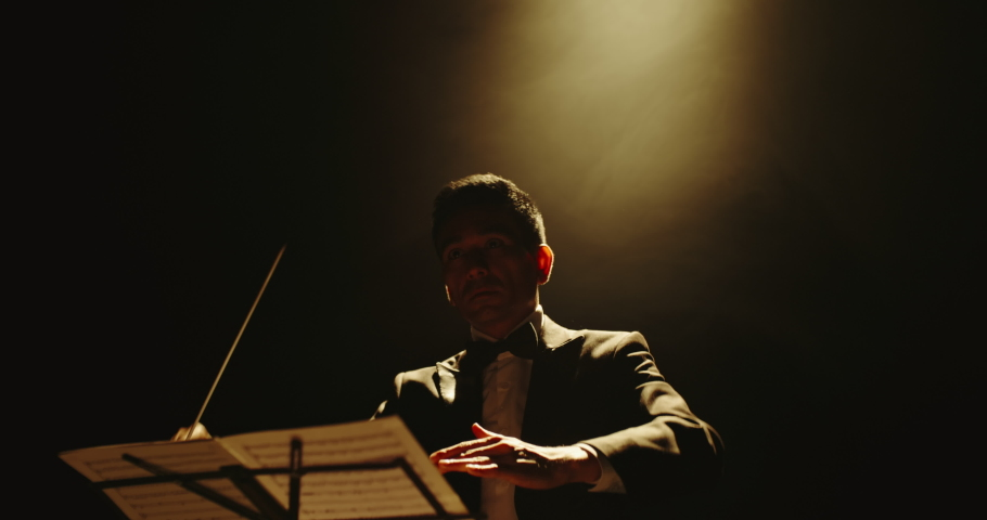 Unrecognizable male symphony orchestra conductor wearing black tux is directing musicians in orchestra pit by moving his hands and baton, studio shot on black background 4k footage