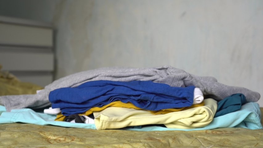 Pile of clothes on the bed. Woman Cleans Out Her Closet In Her Bedroom   Shutterstock HD Video #1033205276