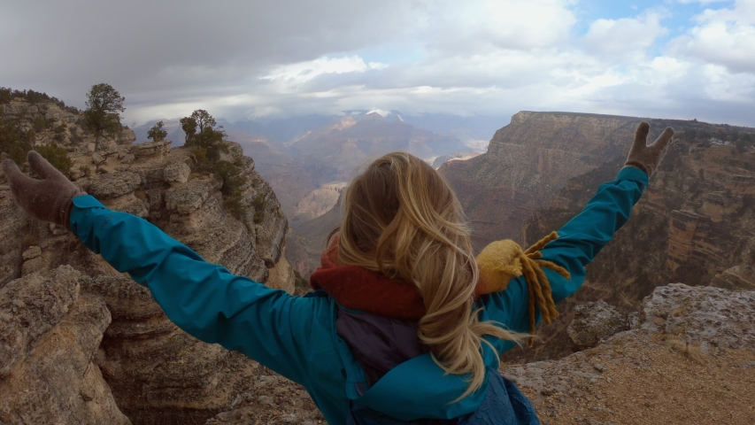 Hiker stands above Grand Canyon arms wide open. Young woman hiking in the Grand Canyon