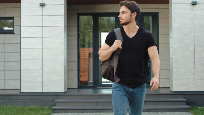 Casual man going down stairs from modern building with backpack. Portrait of male employee leaving office building. Caucasian programmer going outside luxury house. Handsome man leaving apartments Royalty-Free Stock Footage #1033208264