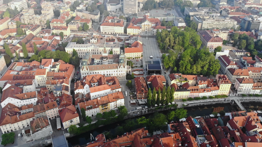 Fly over Ljubljanica river and Congress square in Ljubljana city center, Slovenia. Drone video, aerial view. Summer morning haze. Royalty-Free Stock Footage #1033208423