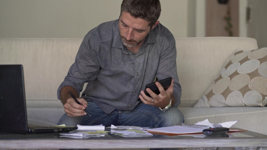 Young attractive and busy man at living room sofa couch accounting monthly expenses and debt payments using calculator counting domestic finance income and tax paperwork at modern apartment  | Shutterstock HD Video #1033209095