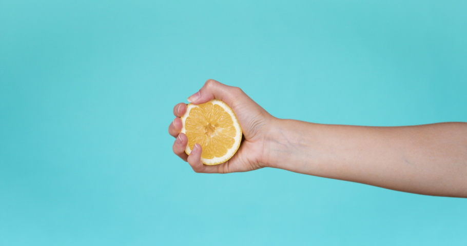 Slow Motion squeeze juice from lemon, hand squeezes half yellow lemon. close-up. Slow motion. Turquoise background.