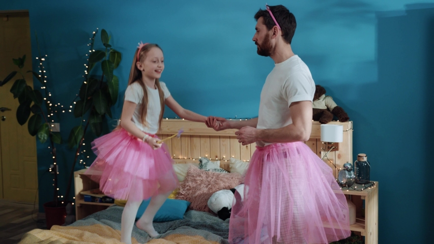 Happy fairytale birthday home party. Cheerful excited daddy and daughter dressed in fancy cosumes playing and dancing together in bedroom. Magic in the house. Family moments. Royalty-Free Stock Footage #1033225247