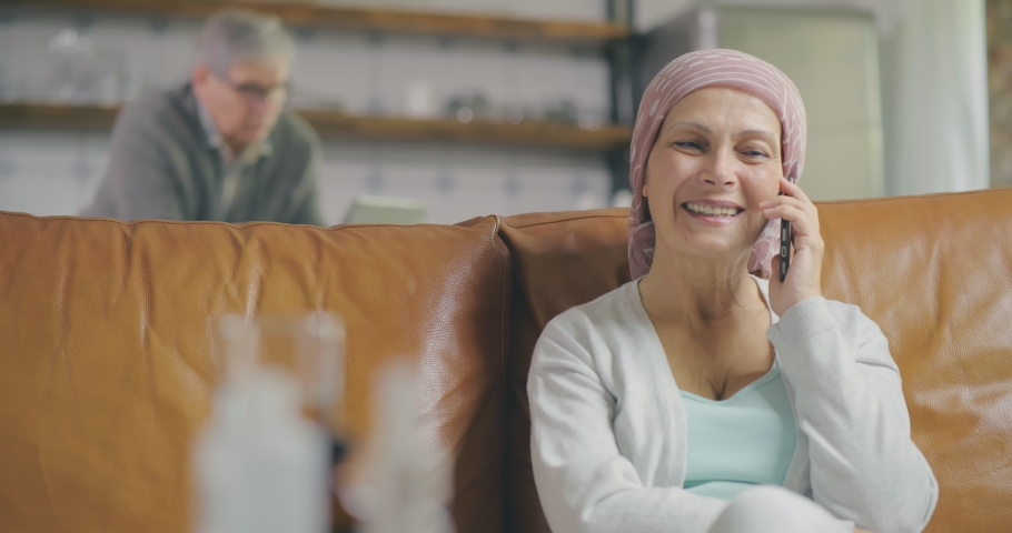 Portrait of happy mature woman recovering after chemotherapy talking on phone and smiling sitting on couch at home