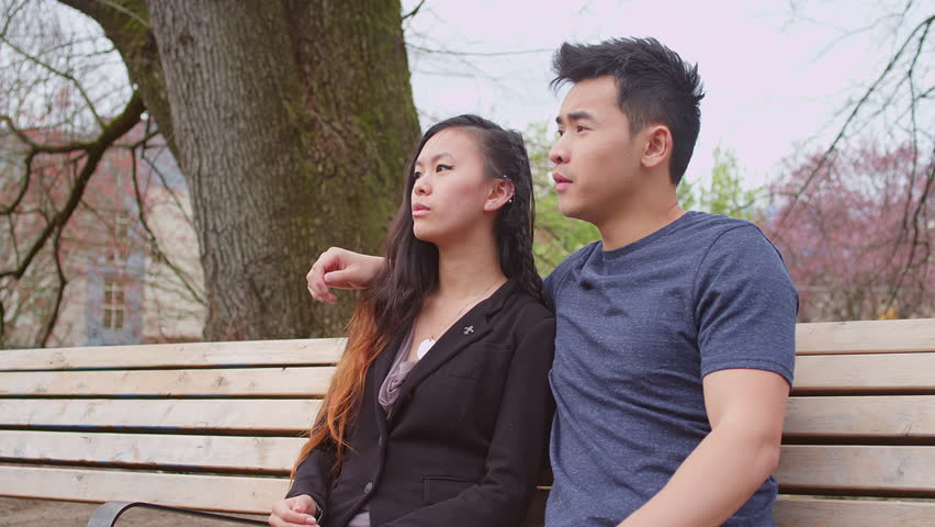 A young couple holding hands and talking on a park bench, then smiling at the camera   Shutterstock HD Video #10332410