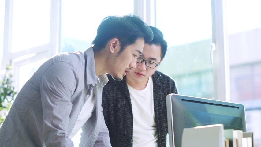 Two young asian businessmen discussing business in office using desktop computer | Shutterstock HD Video #1033245518