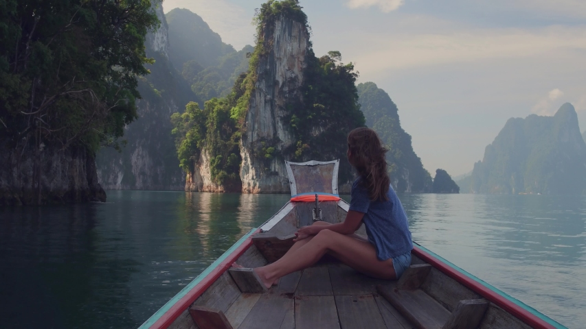 Lifestyle video of pretty travel woman sitting in wood long tail boat on tropical limestone cliffs . Explore and vacation concept. Khao Sok lake, Thailand. Royalty-Free Stock Footage #1033249646