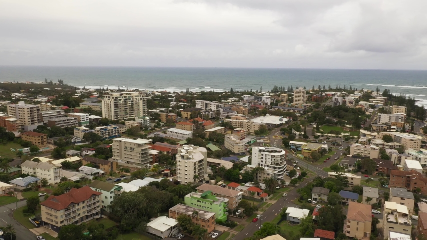 Aerial pan of beach city with strong ocean waves under dark clouds with rained on trees Filmed At Australia Queensland Sunshine coast Caloundra wide shot