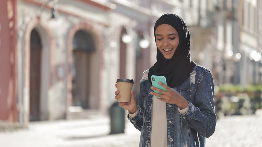 Young muslim woman wearing hijab headscarf walking in the city center, using smartphone and drinking coffee. Communication, online shopping, social network concept.