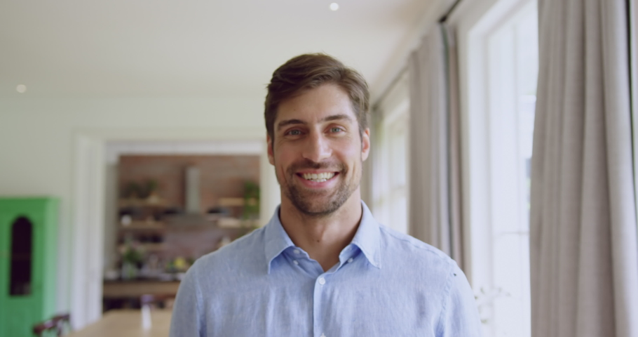 Front view of Caucasian man standing in living room at home. He is smiling and looking at camera 4k | Shutterstock HD Video #1033259390