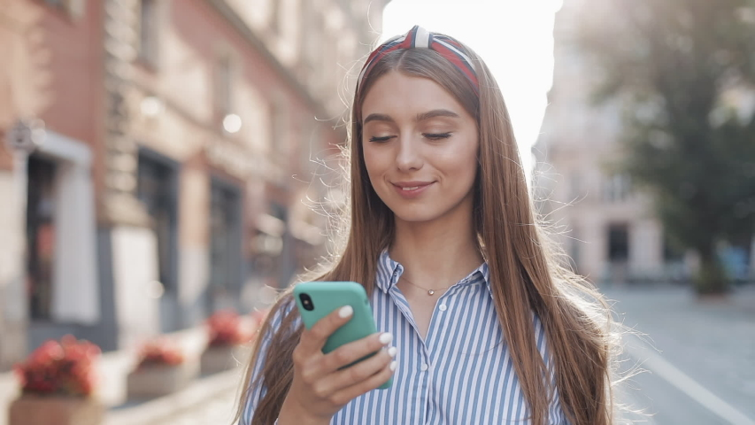 Smiling young woman wearing in blue and white striped dress shirt walking around old street using smartphone. Communication, social networks, online shopping concept.