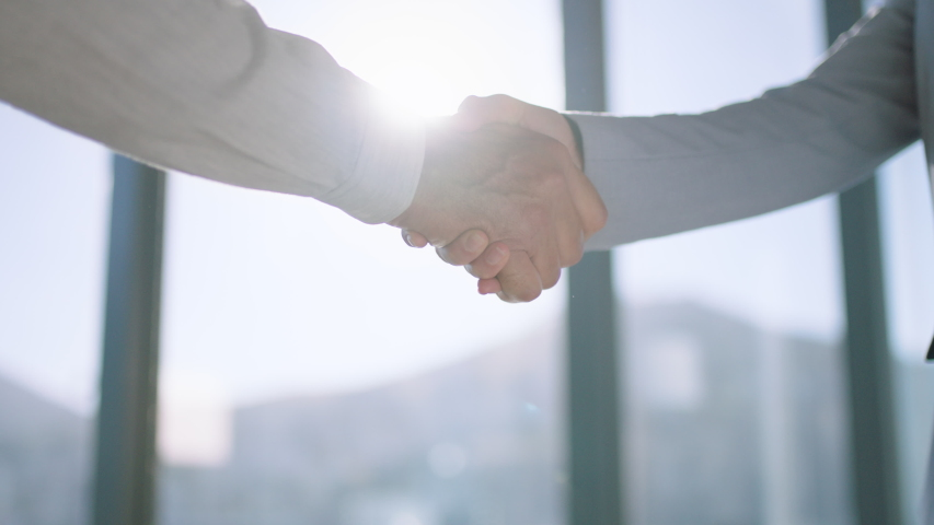 close up business people shaking hands successful corporate partnership deal welcoming opportunity for cooperation in office 4k footage #1033263017