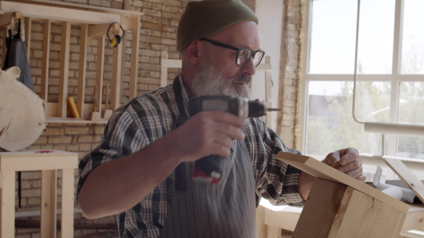 Medium shot of carpenter with beard and spectacles standing at workbench and screwing screw in roof of wooden bird box using electrical screwdriver   Shutterstock HD Video #1033263500