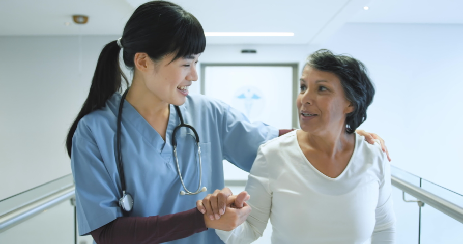 Side view of senior mixed race female patient holding a handrail in a hospital corridor is assisted by a friendly young female Asian doctor.